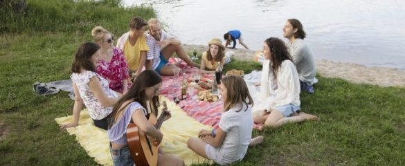 A group of people sitting besides the river